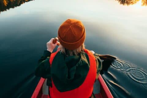 Henkilö meloo järvellä.