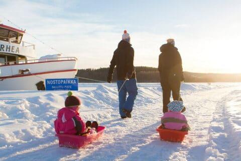 Kaksi aikuista vetää lapsia pulkassa Jyväskylän Lutakon satamassa.