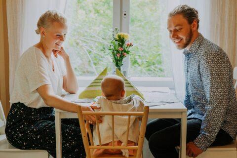 Kaksi aikuista ja yksi lapsi istumassa ravintolan pöydässä