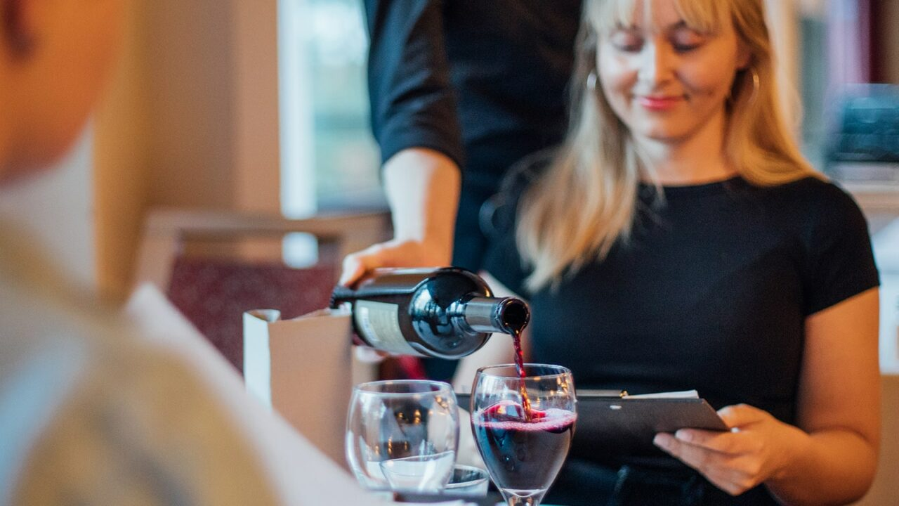 Waitress pouring wine for customers in a restaurant