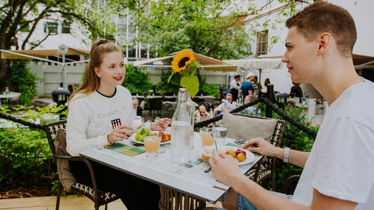 Two persons eating at a terrace