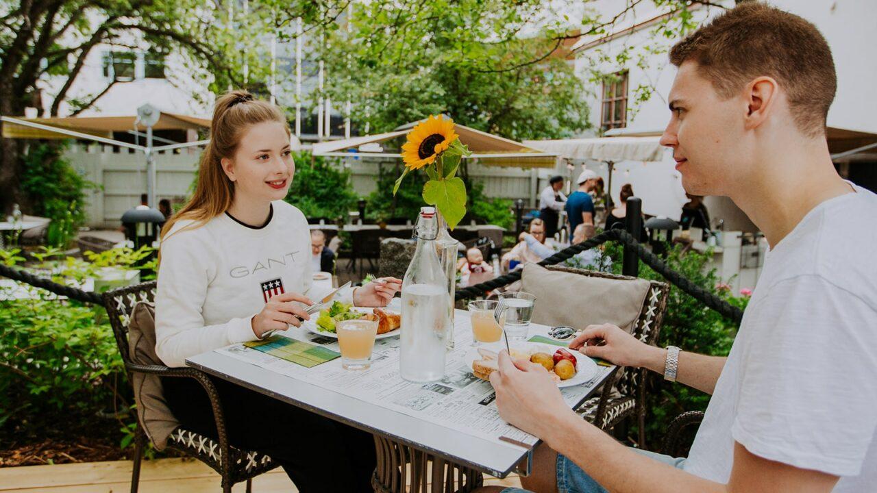 Kaksi henkilöä syömässä terassilla