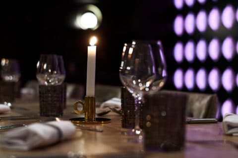 A table in a restaurant with candles and wine glasses.