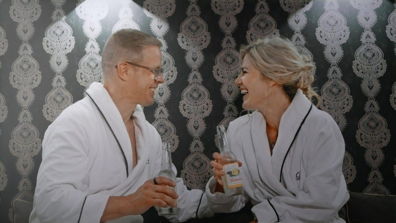 Kaksi henkilöä nauravat kylpytakeissa virvoitusjuomat käsissään.