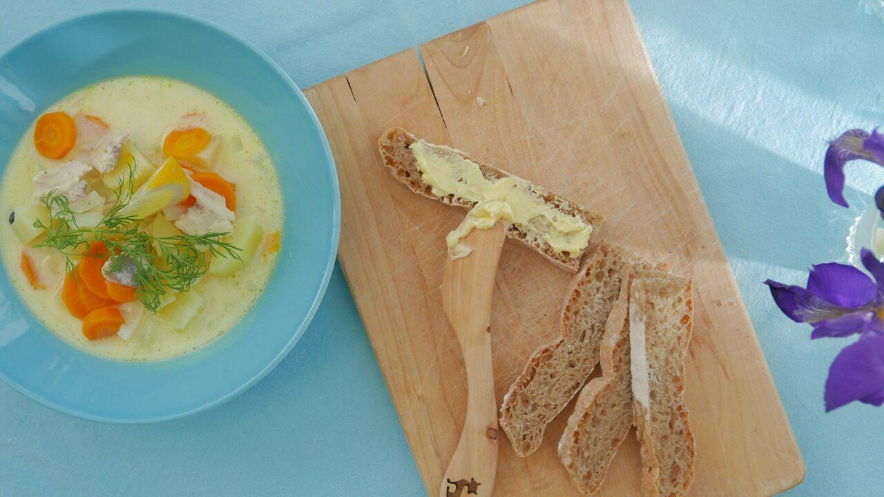 Kalakeittoa ja vaaleaa leipää sinisellä pöydällä