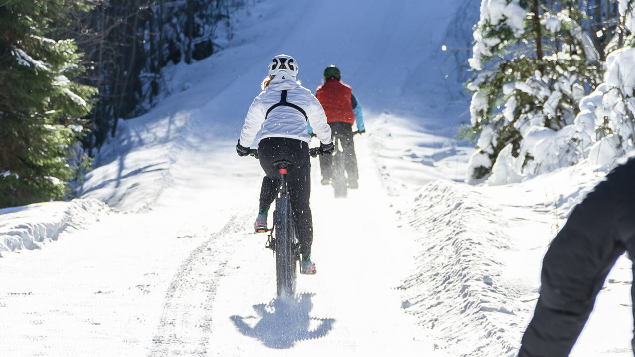 Henkilöitä pyöräilemässä e-fatbikella lumisessa ja aurinkoisessa talvimaisemassa