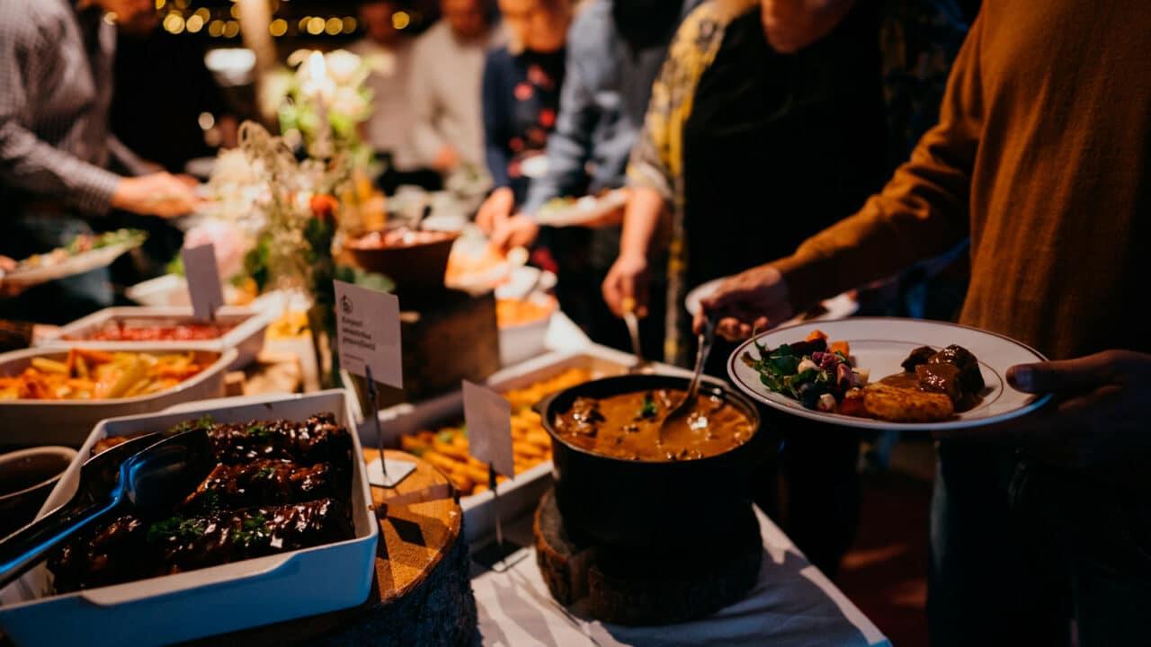 Ihmiset ottamassa ruokaa juhlapöydästä