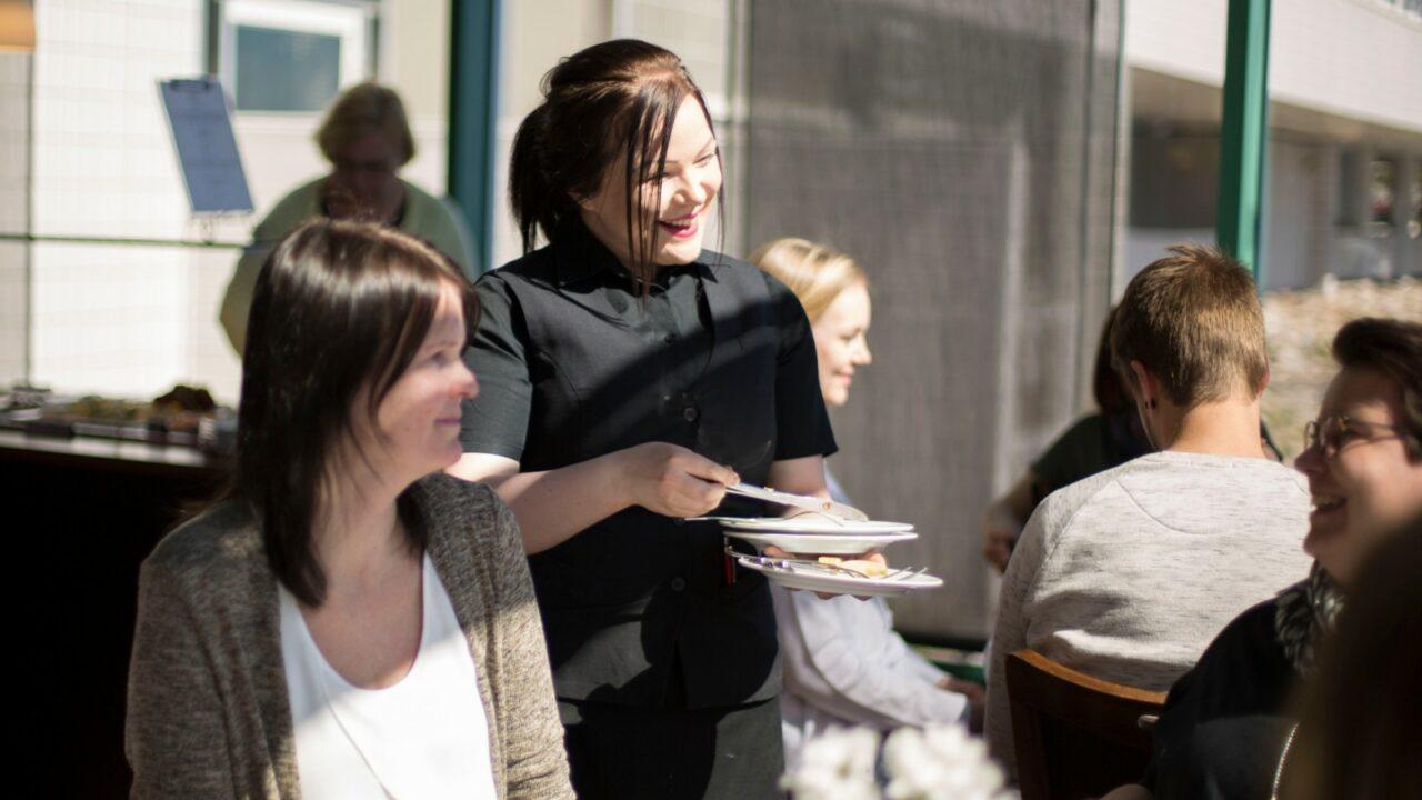 Hotelli Alban tarjoilija palvelee ruokailemaan tulleita asiakkaita hymyssä suin