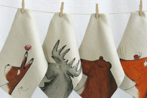 Eläinkuvioituja pyyhkeitä kiinnitettynä pyykkipojilla narulle.