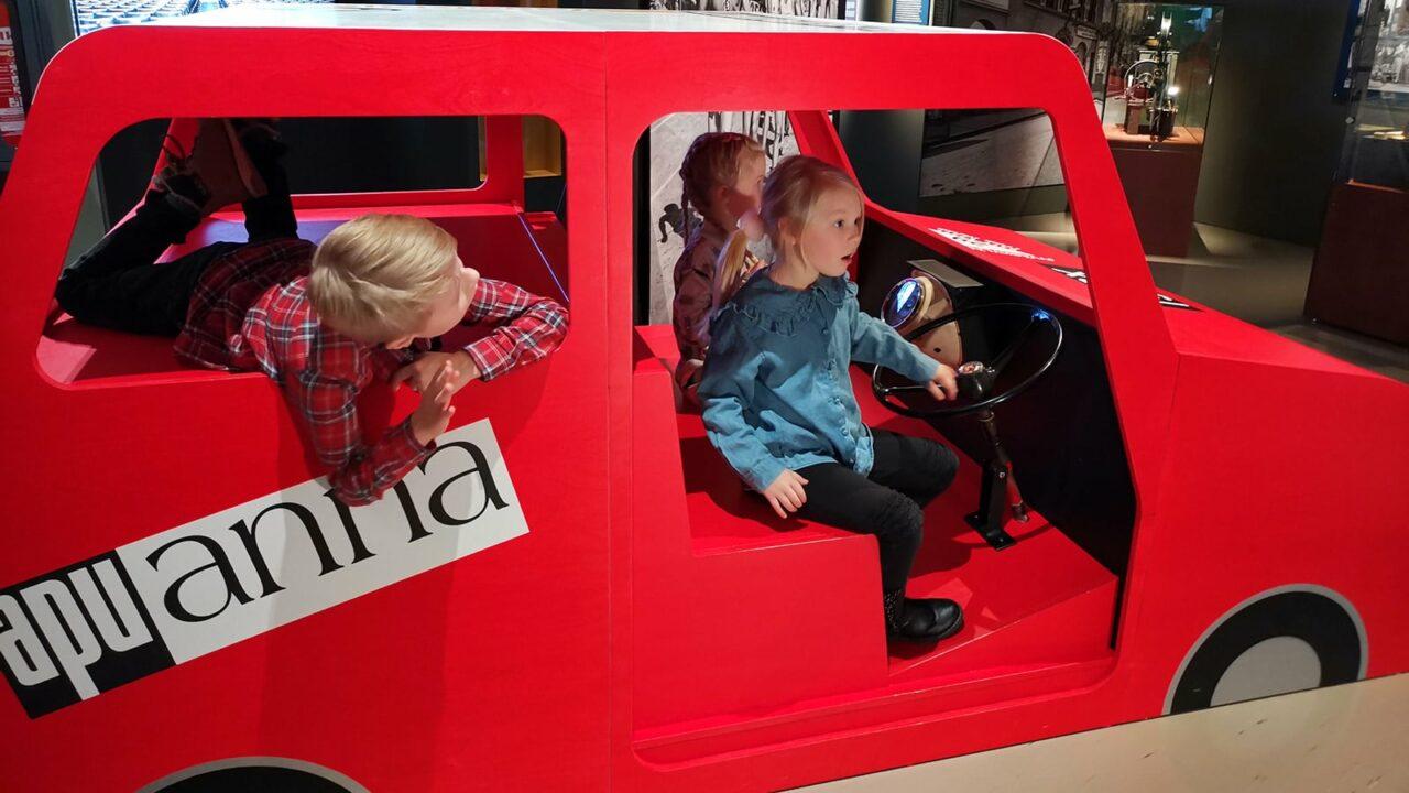 Lapsia ison leikkiauton sisällä Keski-Suomen museossa.