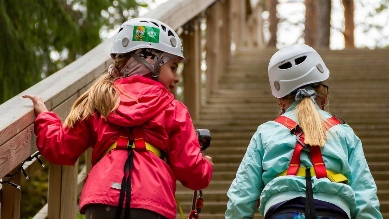 Kaksi lasta kiipeää portaita ylös Laajavuoren Seikkailupuistossa.