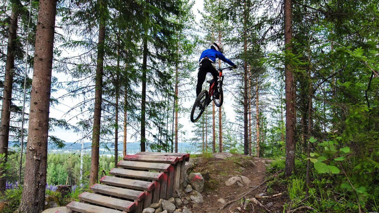 Pyöräilijä hyppää ilmaan Bikeparkin hyppyristä pyörän kanssa.