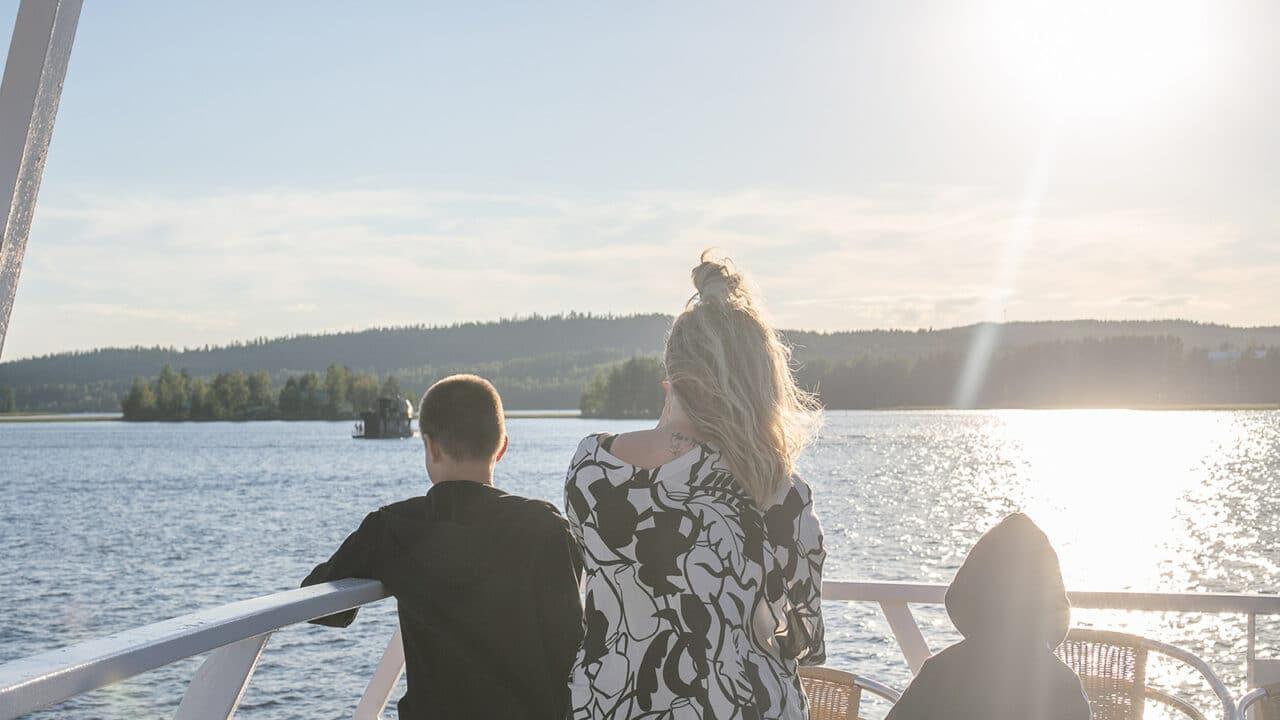 Kolme henkilöä risteilylaivan kannella.