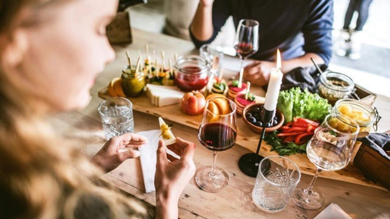 Savutuvan Apajan juhlapöytään on katettu viiniä ja pientä naposteltavaa