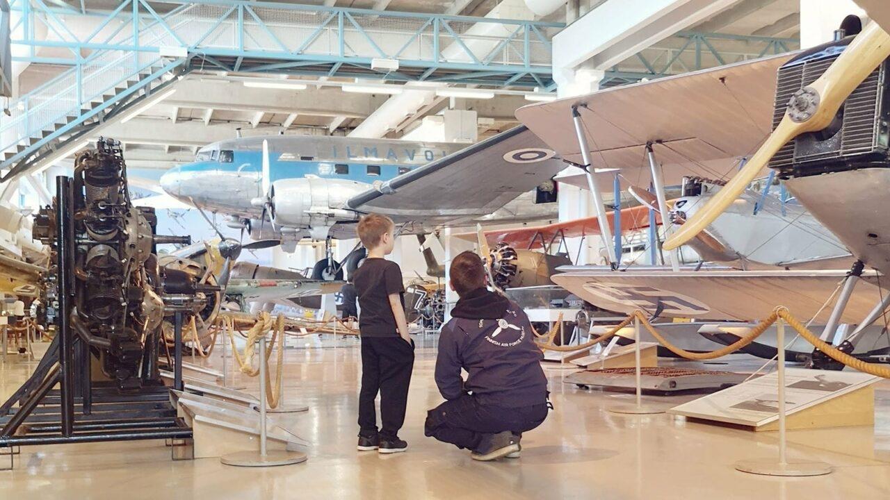 Aikuinen ja lapsi katsovat lentokonetta Suomen Ilmavoimamuseossa.