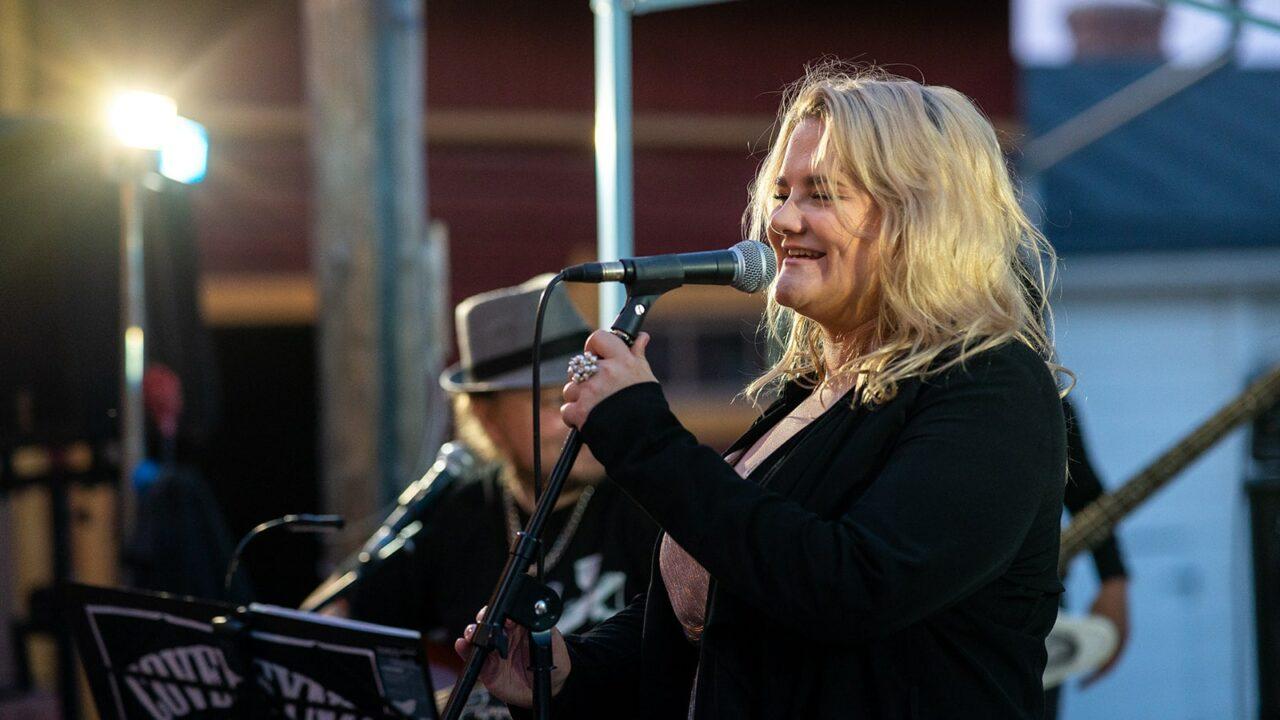 Henkilö laulaa mikrofoniin Toivolan vanhalla pihalla.