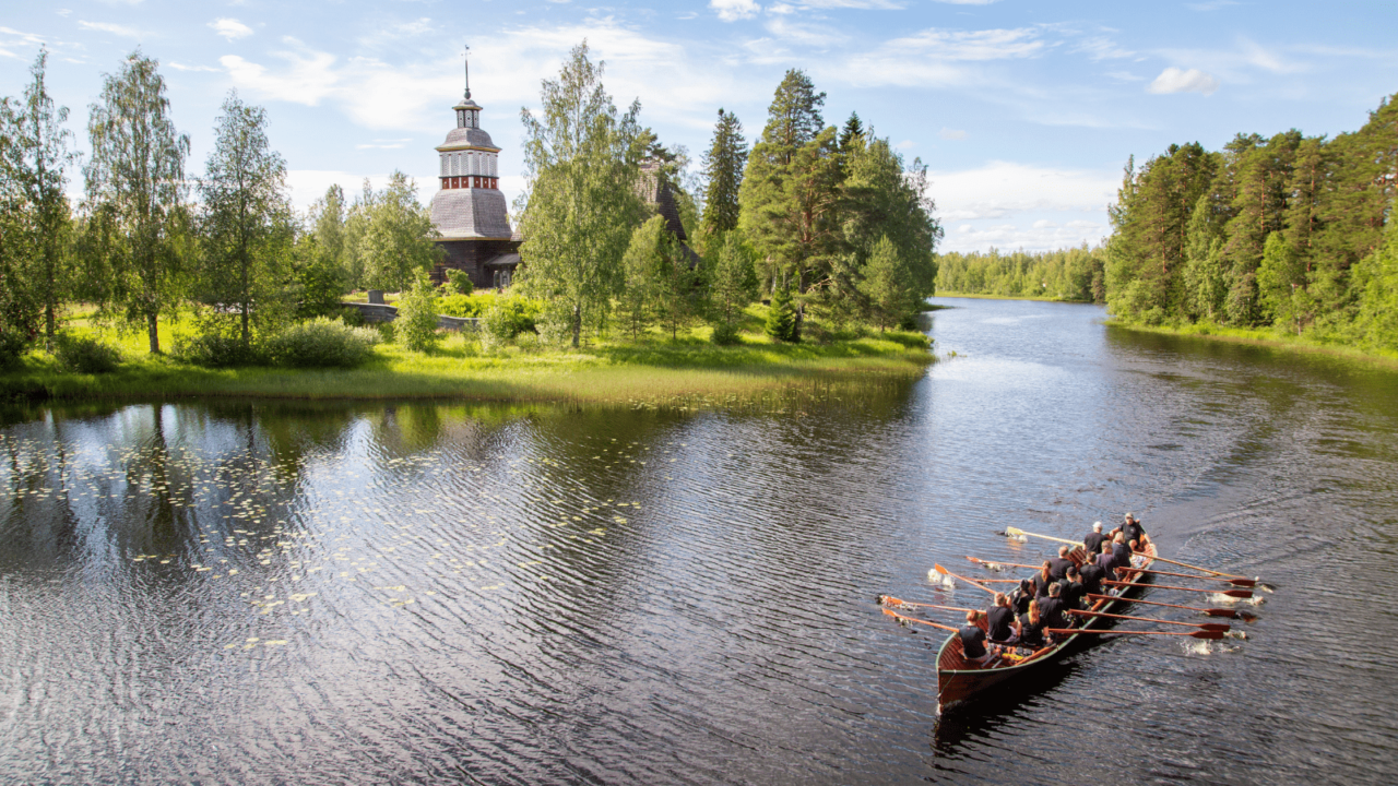 A church boat rowing on water in front of the Petäjävesi Old Church