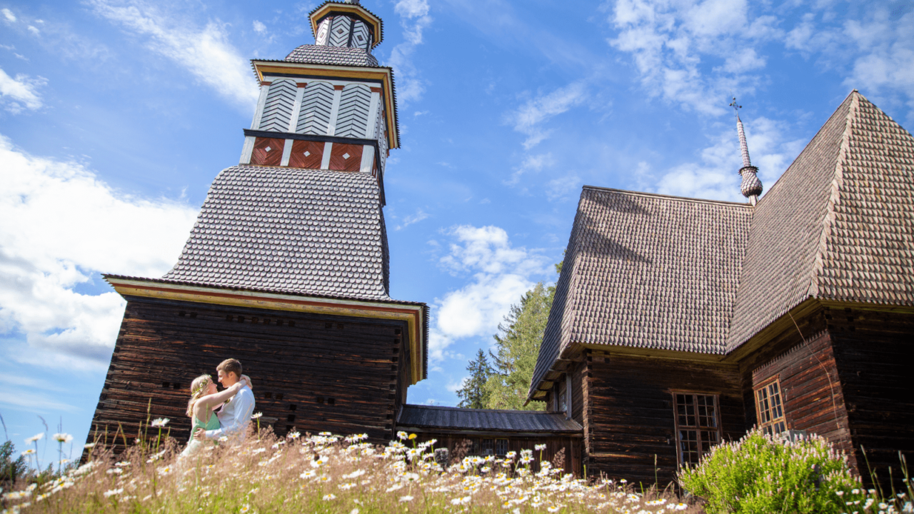 Two people kiss in front of the Petäjävesi Old Church