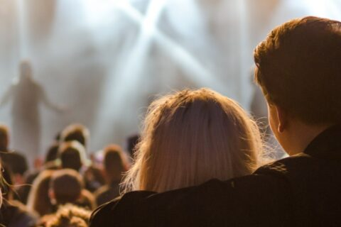 Two people watching a concert while cuddling