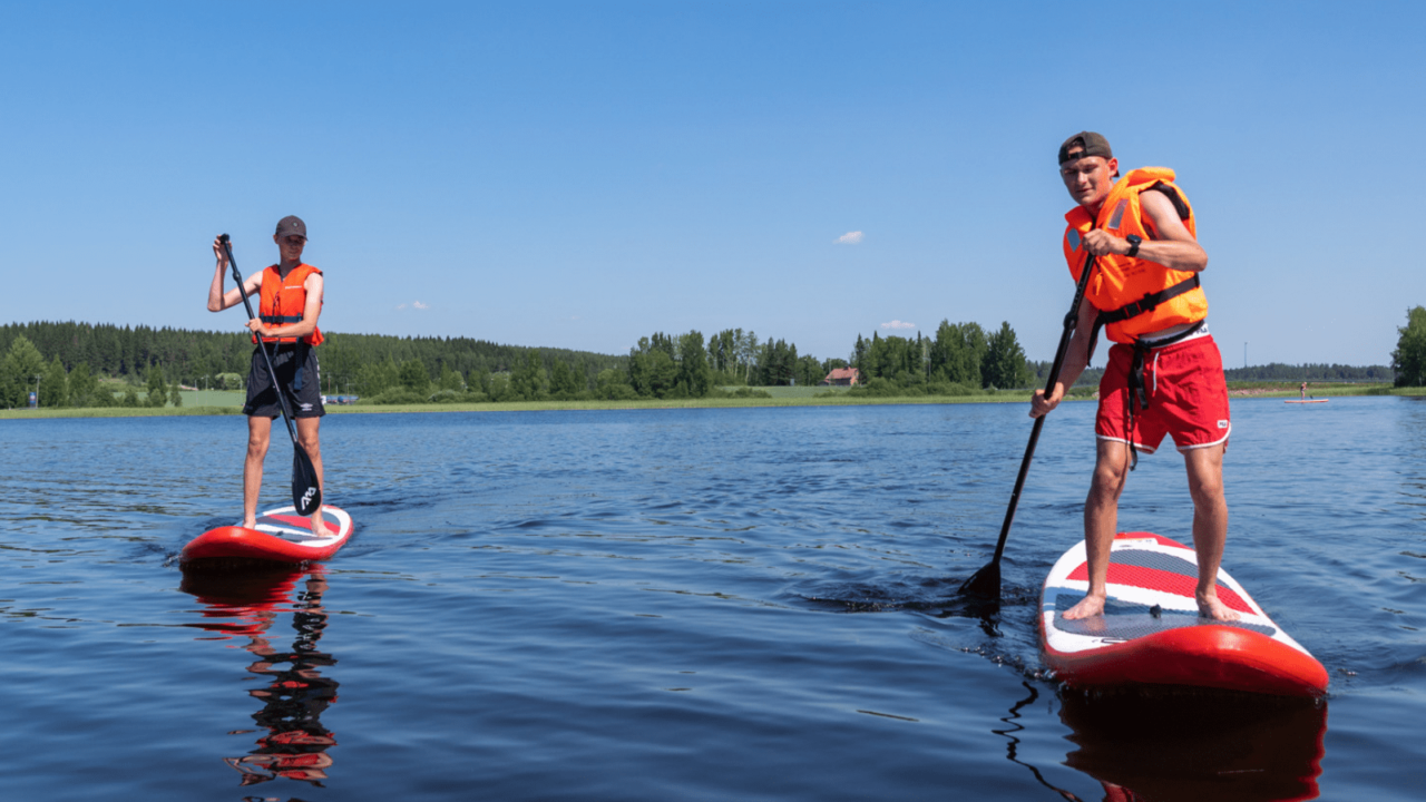 Two people sup-boarding on a lake