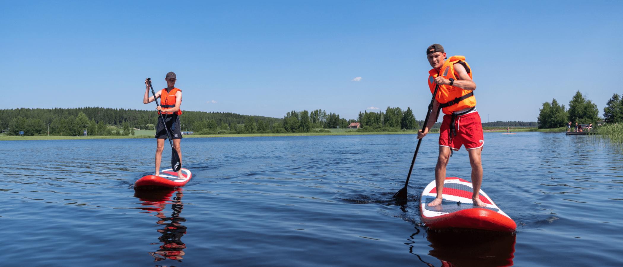 Kaksi henkilöä sup-lautailemassa järvellä