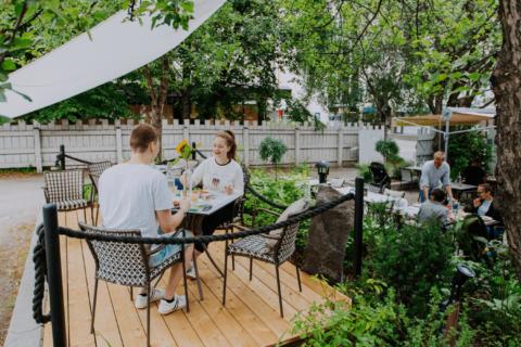 Kaksi henkilöä syömässä puutarharavintolassa