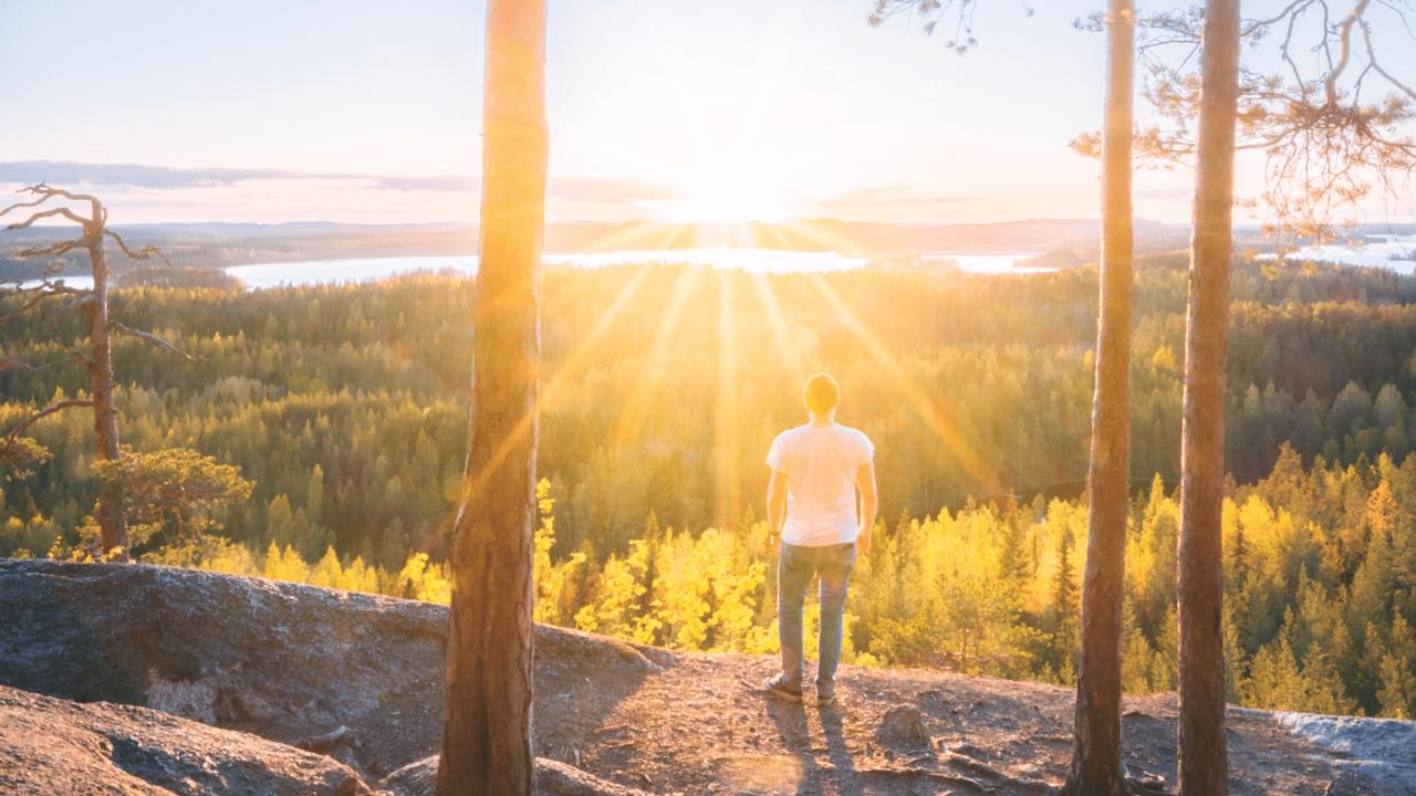 Henkilö Hyyppäänvuorella auringonlaskun aikaan