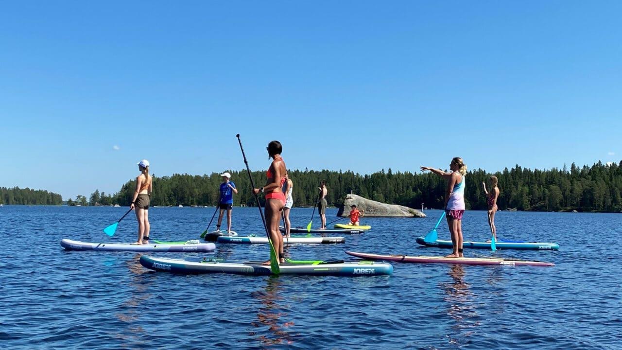 Ihmisiä seisomassa Sup-laudoillansa järvellä