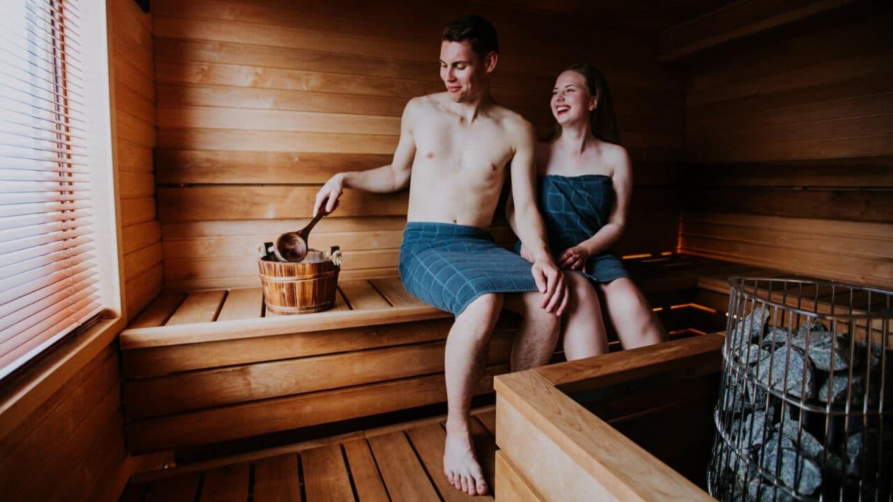 Kaksi henkilöä saunomassa Rhealla.