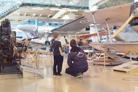 Kaksi henkilöä katsovat lentokonetta Suomen ilmavoimamuseossa.