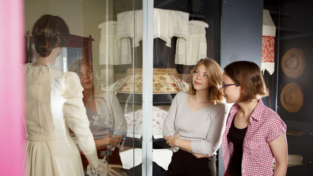 Kaksi henkilöä katsomassa mekkoa näyteikkunassa Suomen käsityön museossa.