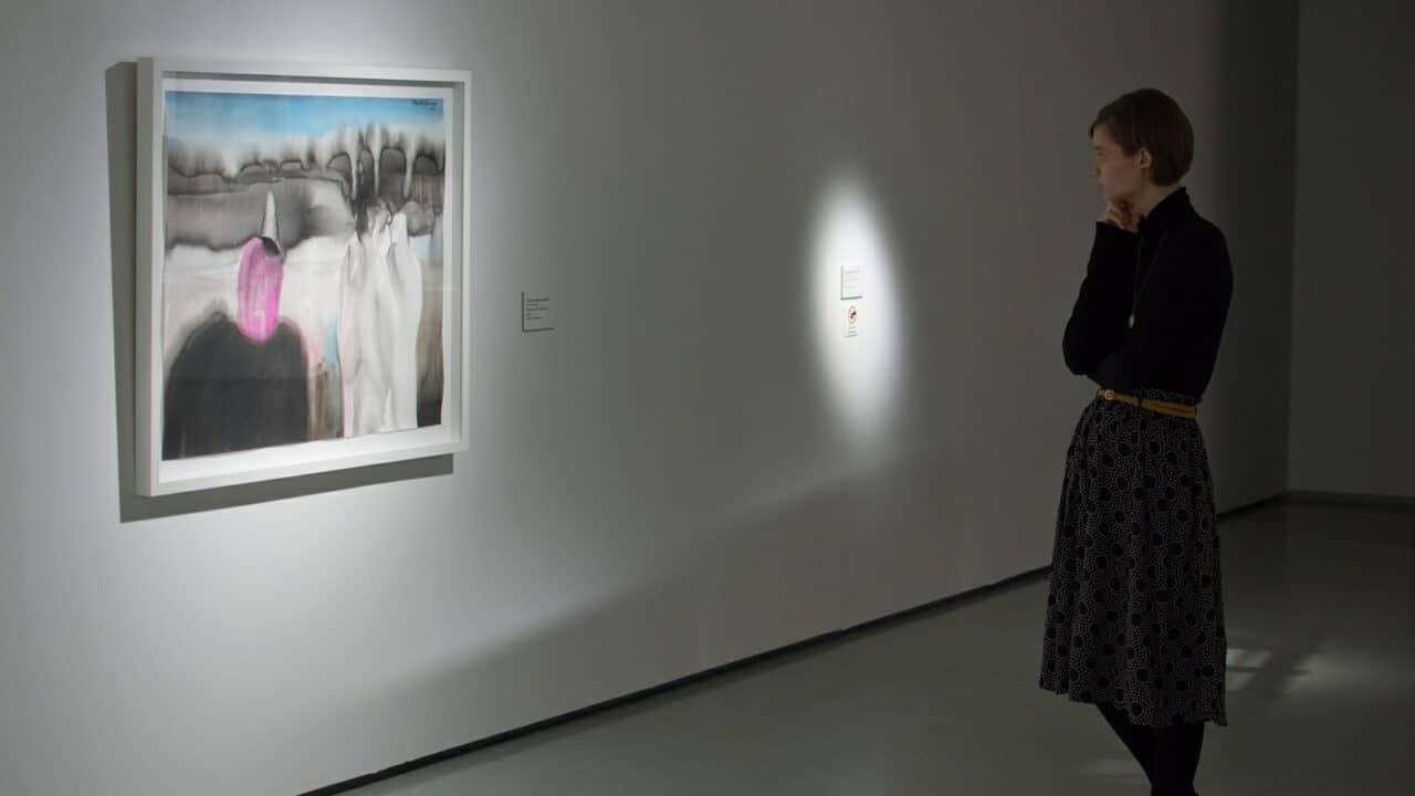 Henkilö katsoo taulua taidemuseossa.