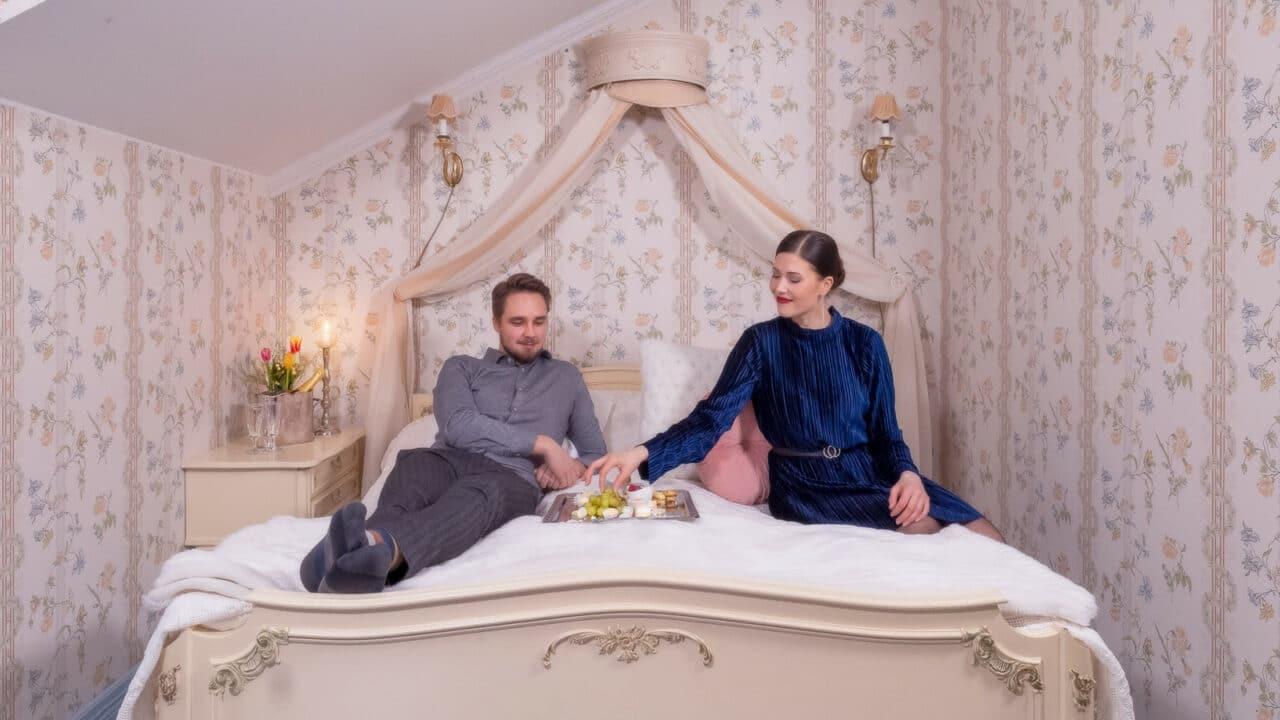 Kaksi henkilöä istuu sängyllä ja syö naposteltavia tarjottimelta.