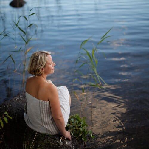 Henkilö istuu järven rannalla kiven päällä pyyhe ympärillä