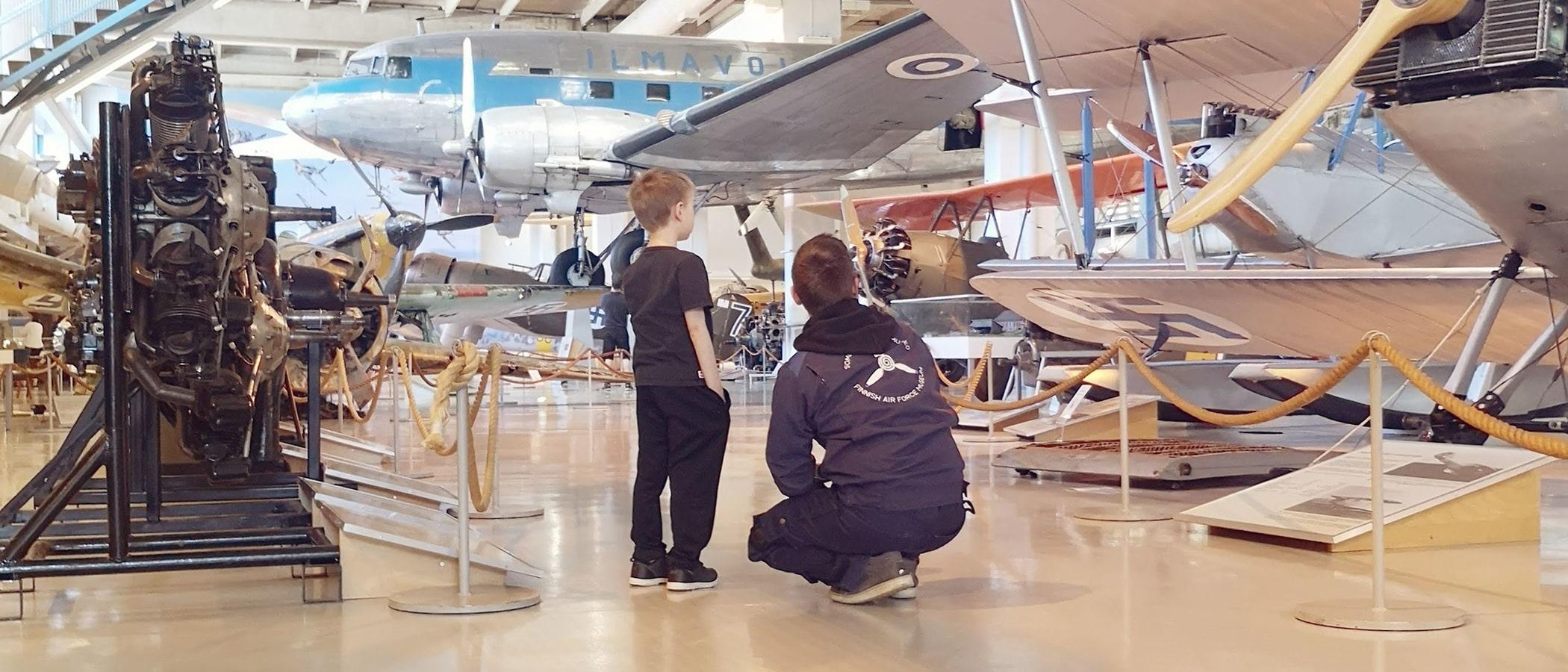 Lapsi ja aikuinen katsovat lentokonetta Suomen Ilmavoimamuseossa.