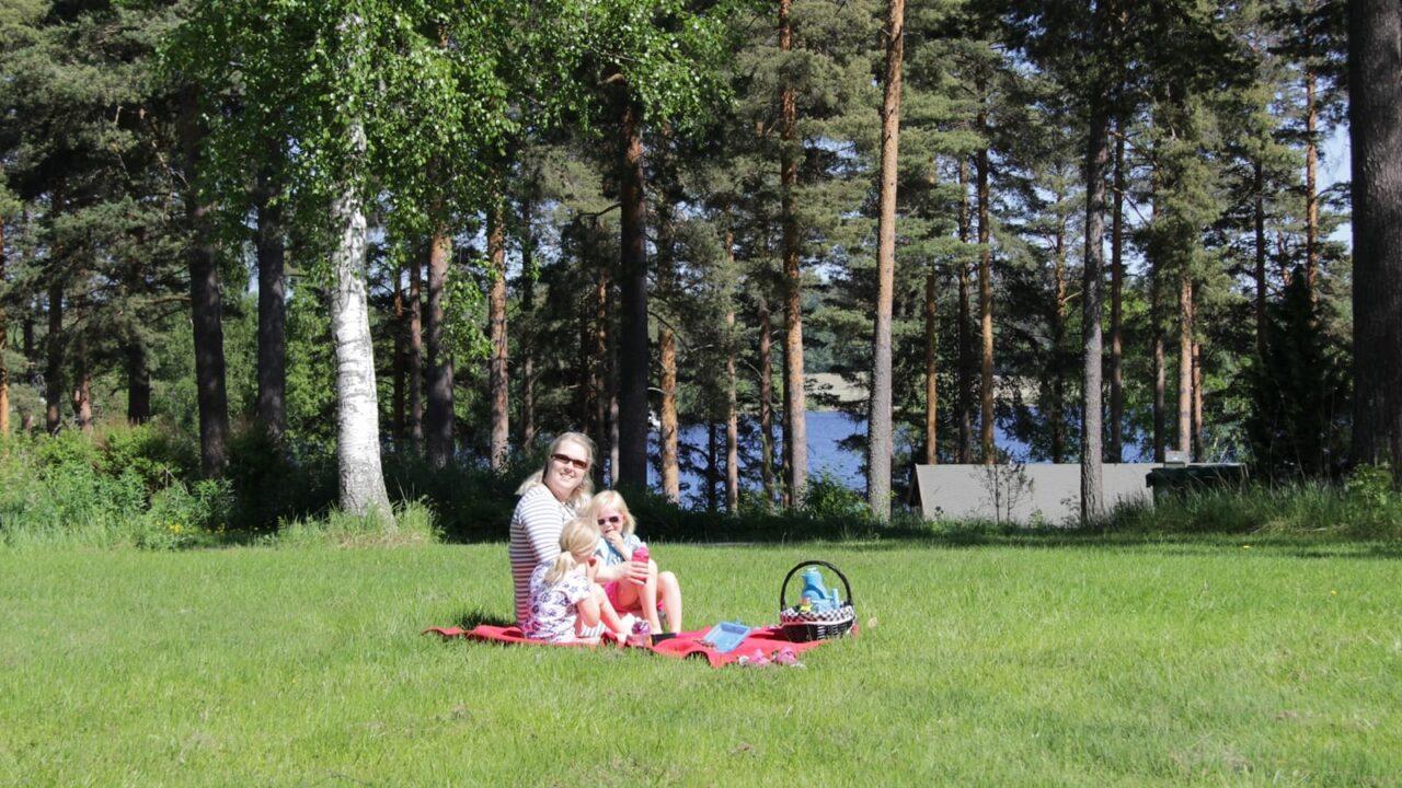 Kolme henkilöä piknikillä nurmella Tähtelässä