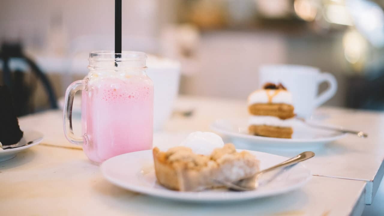 Pink drink with whistle and pastry on a plate