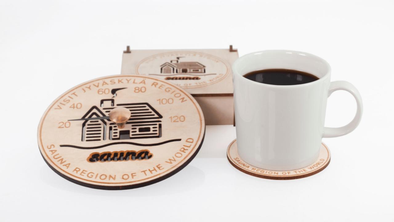 Saunamittari, lasinalusia ja kahvikuppi.