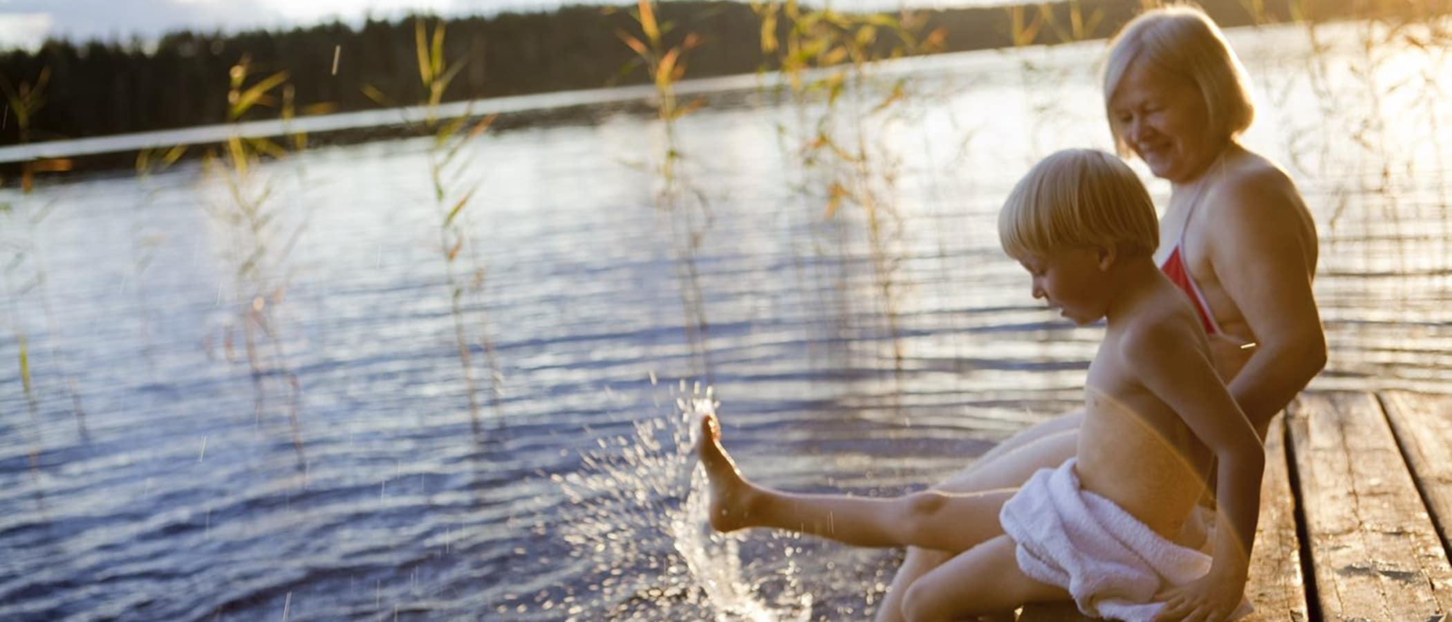 Aikuinen ja lapsi polskuttelemassa laiturilla auringon laskiessa