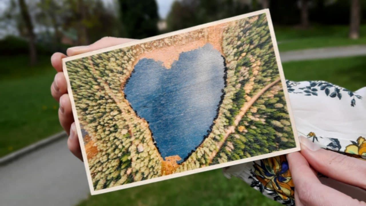 Postikortti, jossa on sydämenmuotoinen järvi.