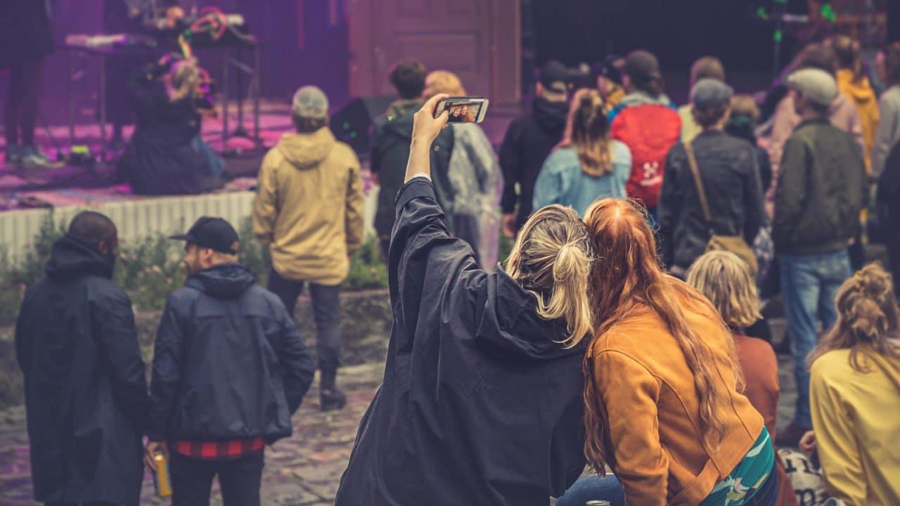 Kaksi henkilöä ottamassa selfietä puistojuhlissa.