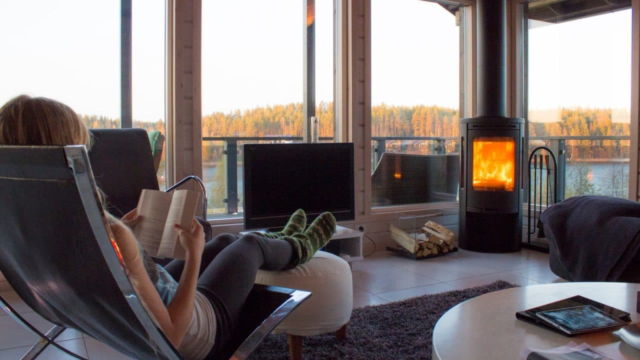 Henkilö istuu mökin nojatuolissa kirjaa lukien. Takassa on tuli ja ikkunoista avautuu maisema järvelle ja metsään.