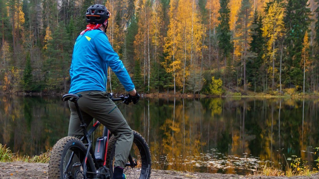 Maastopyöräilevä henkilö on pysähtynyt katsomaan syksyistä maisemaa