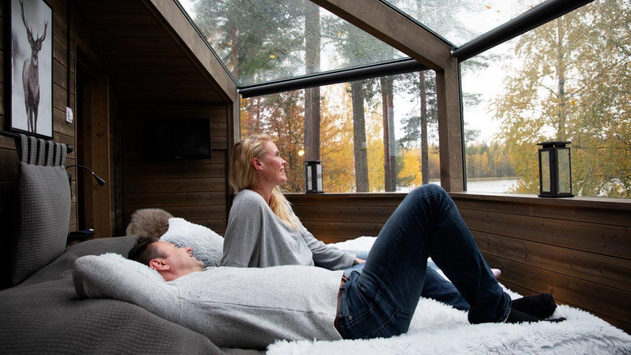 Kaksi ihmistä makoilee sängyllä Revontuli Resortin lasi-iglussa.