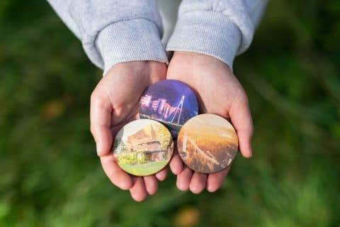 Puisia magneetteja henkilön käsissä. Taustalla vihreää nurmikkoa.