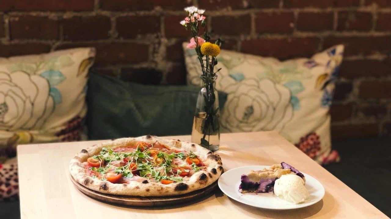 Ravintolan pöydällä on artesaanipizza sekä kakkupala