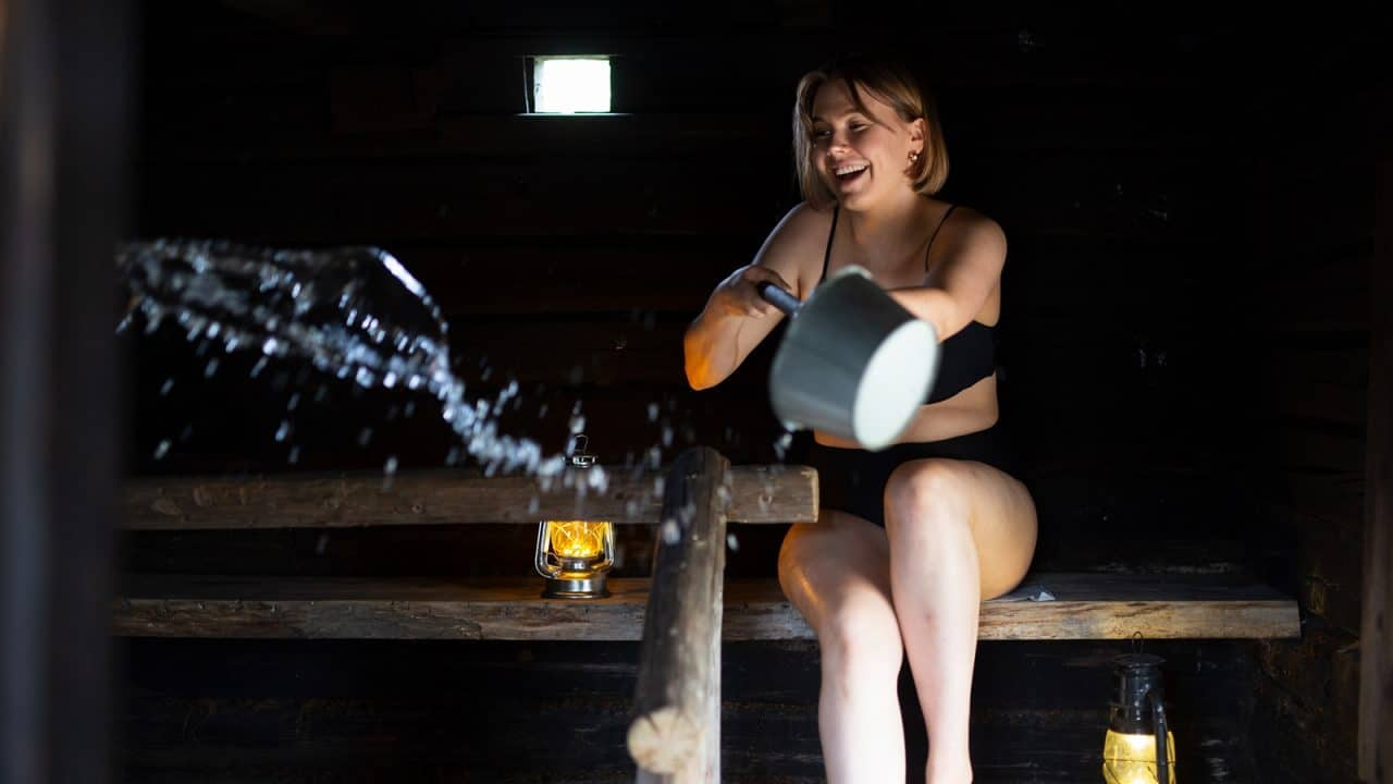 Person bathing in a sauna throwing water to the hot stones