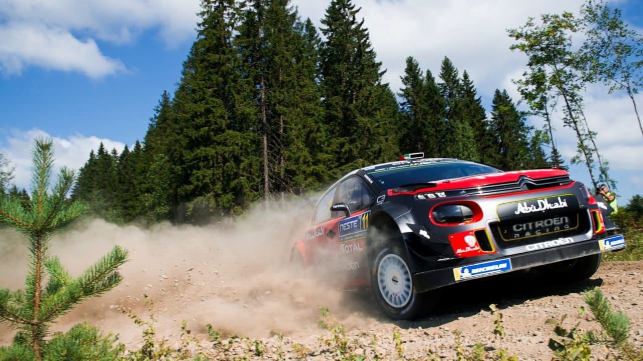 Racecar driving on a gravel road in the forest landscape