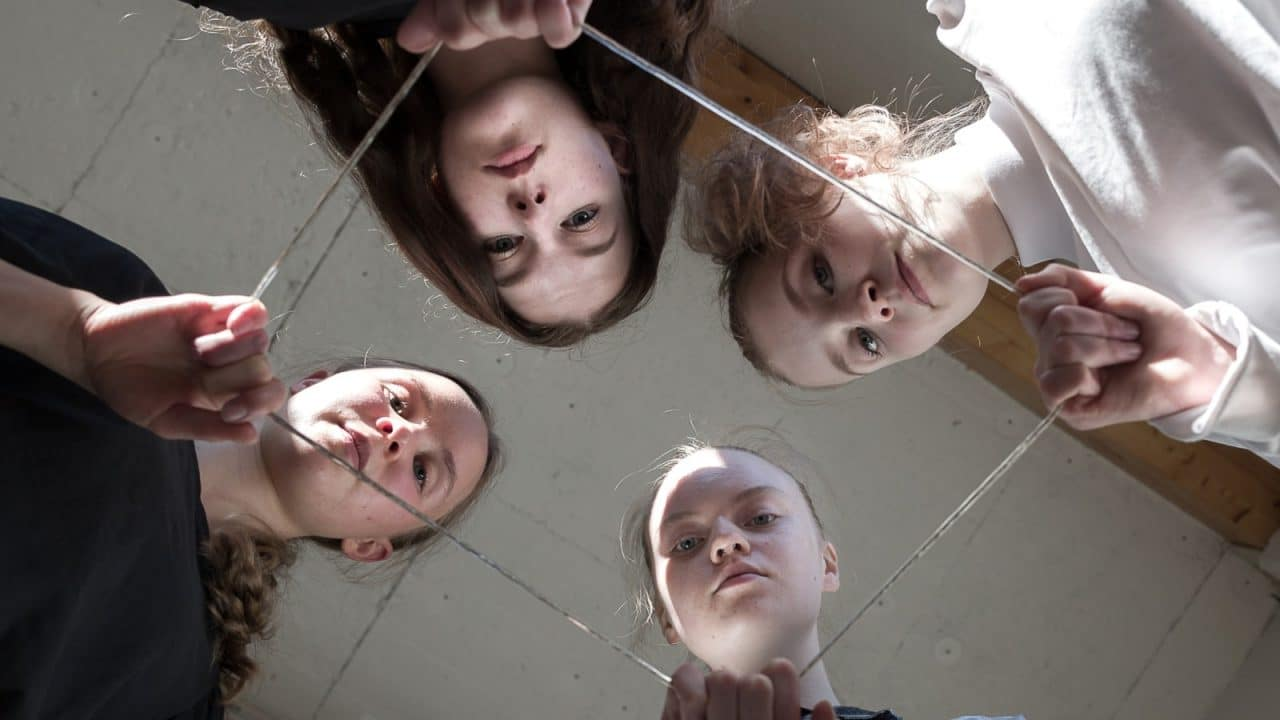 Picture of four persons holding a wire and looking down captured from below